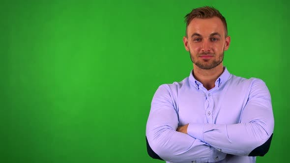 Thumbnail for Young Handsome Business Man Smiles To Camera with Folded Arms - Green Screen - Studio