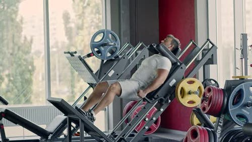 Sporty Man Doing Exercises with Leg Press Machine at Fitness Gym, Hard Squats Workout