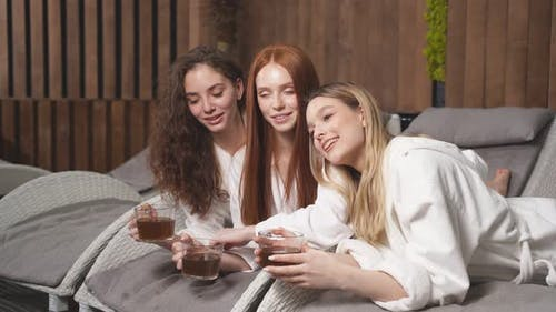 Three Young Ladies Clothed Bathrobe Lying on Deckchairs Talking and Drinking Tea