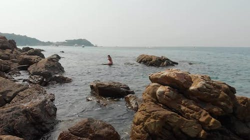 Lady Climbs Up Big Stone in Clear Blue Ocean Against Sky
