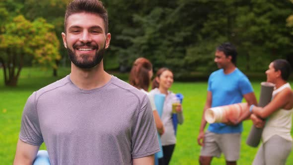 Smiling Man with Yoga Mat Over Group of People