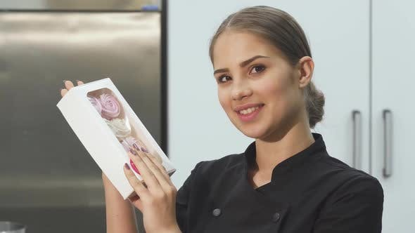 Thumbnail for Attractive Female Baker Smiling to the Camera Holding a Bow of Marshmallows