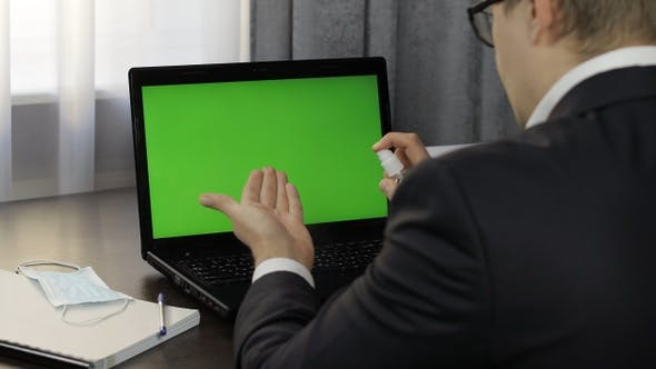 Thumbnail for Man Takes Sanitizer Bottle and Use Near Laptop with Green Screen. Distance Work