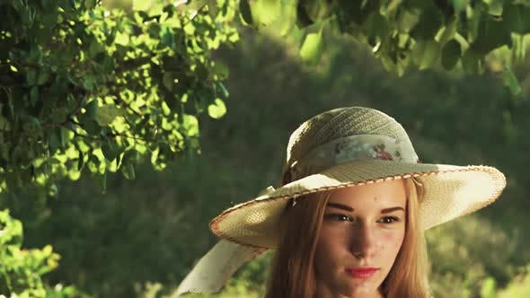 Thumbnail for Girl in a Hat Poses for Cameras in a Green Forest. Slow Motion