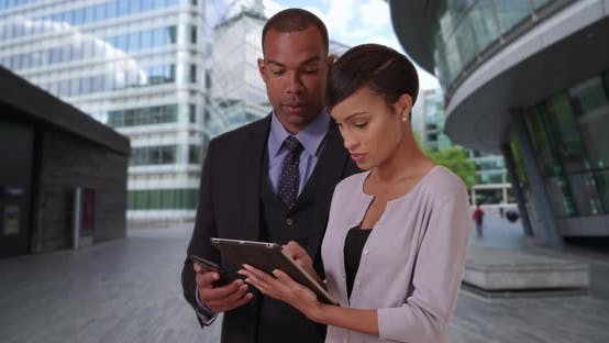 Thumbnail for Black male and female business colleagues look over data on tablet