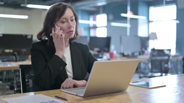 Thumbnail for Cheerful Middle Aged Businesswoman Talking on Smartphone at Work