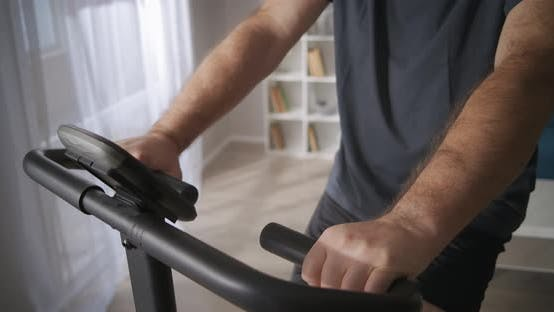 Middleaged Man Is Training on Exercise Bicycle at Home Healthy Lifestyle Keeping Physical Condition