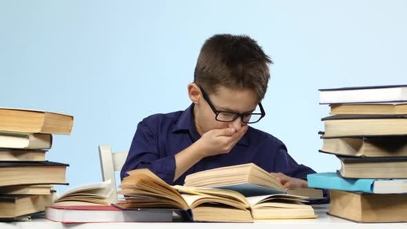 Boy Sits at the Table and Wearily Leafing Through a Book. Blue Background