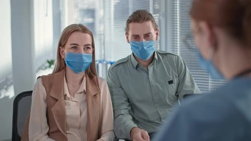 Married Couple Wearing Medical Masks Receive Negative News During Doctor Consultation in Hospital
