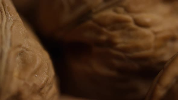 Thumbnail for Cinematic, rotating shot of walnuts in their shells on a white surface - WALNUTS