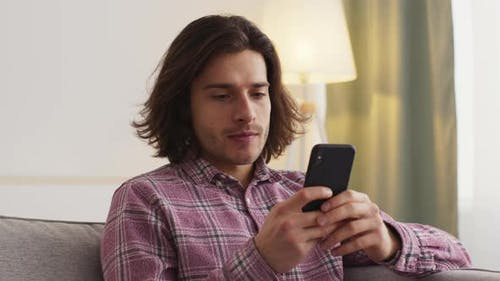 Close Up of Young Man Sitting on Couch at Home Web Surfing in Social Media on Smartphone