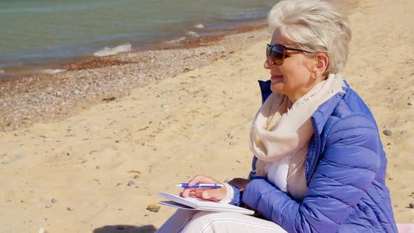 Thumbnail for Senior Woman Writing To Notebook on Summer Beach