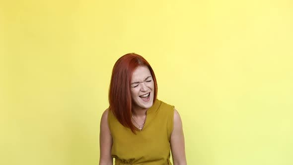 Thumbnail for Emotional Girl with Red Hair Shouting Over Yellow Background.