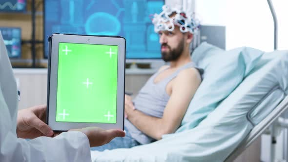 Doctor in a Neurology Clinic Holding Tablet with Green Screen