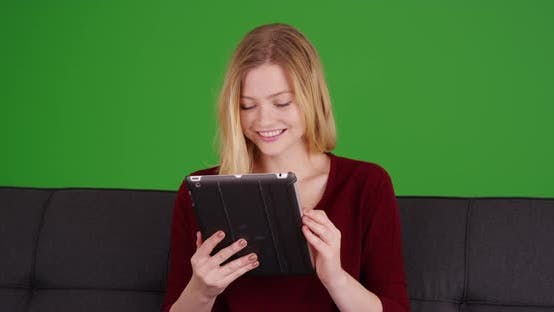 Thumbnail for Joyful portrait of young millennial woman sitting on sofa on green screen
