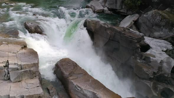 Thumbnail for Wilderness Aerial Of Raging River Waterfall With Green Water Moving Slow Motion In Canyon Rocks