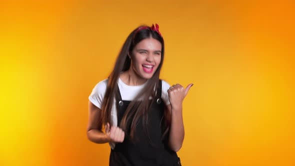 Thumbnail for Surprised Woman on Yellow Background. Girl with Long Hair Shows Yes Gesture