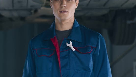 Close Up Portrait of Young Handsome Mechanic in Garage, Tracking Shot