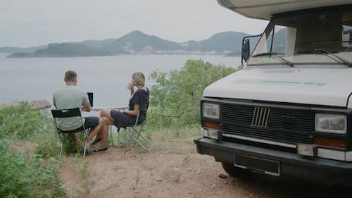 Young  travel couple sitting near motor home RV campervan.