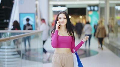 Young Woman with Shopping Bags Talking on Phone