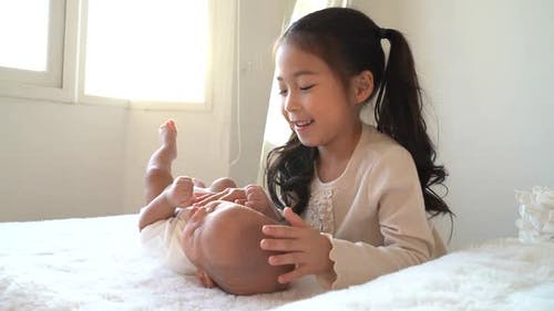 Asian Family of Cute Little Sister Touching Newborn Baby Boy Brother on Bed