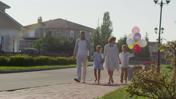 Thumbnail for Happy Family Walking Outdoors with Balloons on Summer Day
