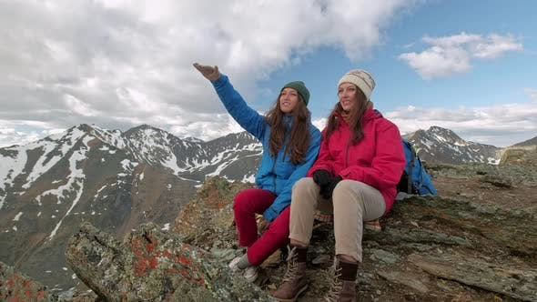 Thumbnail for Happy Young Women Friends Sitting on Fence, Snowy Mountain Landscape Around