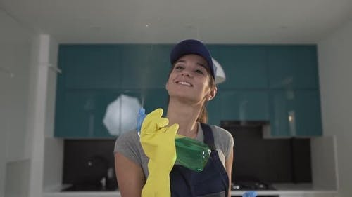 Lovely Young Cleaning Woman in Workwear Spraying Green Detergent