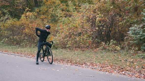 Thumbnail for Male sportive cyclist in black helmet starting his cycling workout in fall park. Slow motion.