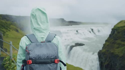Woman Traveler with Backpack in Front of Beautiful Gullfoss Waterfall