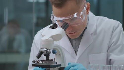 Forensiker Expert Man erforscht Analyse und Beweise im Labor und schaut in das Mikroskop