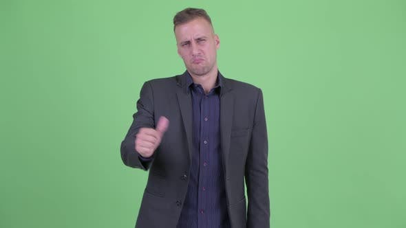 Cover Image for Stressed Businessman in Suit Giving Thumbs Down