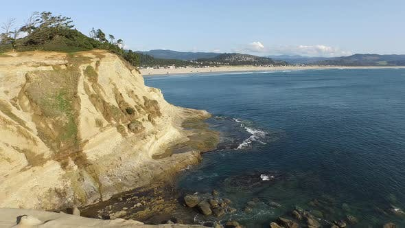 Thumbnail for Aerial shot of backpacker walking on rock overlooking Pacific Ocean