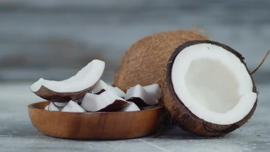 Thumbnail for Pieces of Fresh Coconut on a Wooden Plate Slowly Rotate.