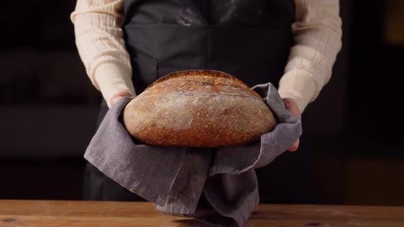 Female Baker with Homemade Bread at Bakery