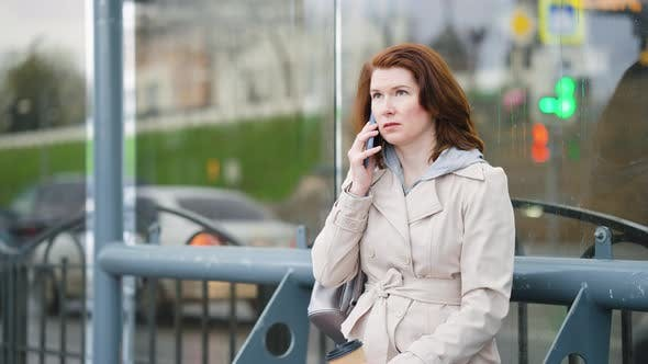 Woman at Bus Stop Talking on Phone