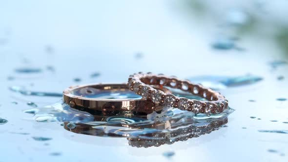 Thumbnail for Precious Metal Jewelry Against Blurred Background. Water Pouring Onto the Wedding Bands