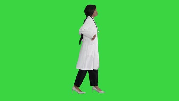 Sad African American Female Doctor Walking with Hands in Her Pockets on a Green Screen, Chroma Key.