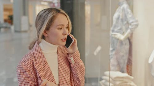 Pretty Young Woman Talking On Phone During Clothes Shopping
