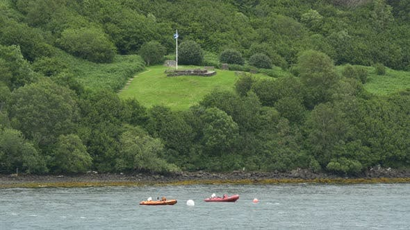 Thumbnail for Inflatable boats anchored near a green hill