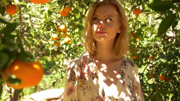 Thumbnail for Young Lady Looking Around at the Oranges on an Early Morning Walk