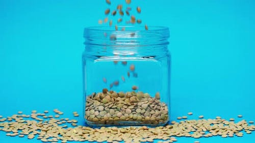 Closeup of Falling Down Lentils Into Glass Jar on Blue Background