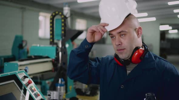 Thumbnail for A Male Factory Worker Puts on a Safety Helmet