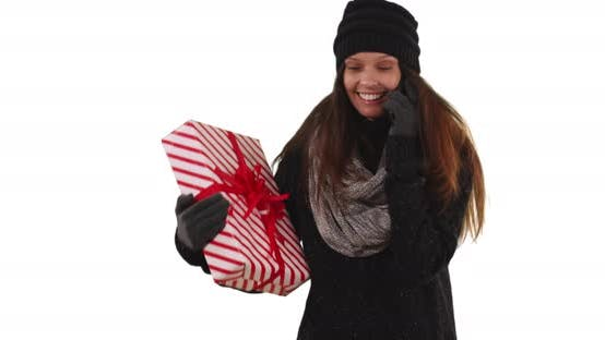 Thumbnail for Woman talking on cellphone while holding Christmas gift on white background