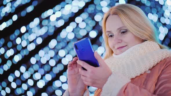Thumbnail for Young Woman Uses Smartphone on the Background of Evening Lights of Christmas Decorations