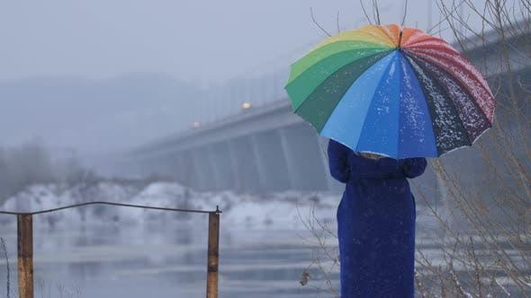 Thumbnail for Woman with Rainbow Umbrella During Snowfall