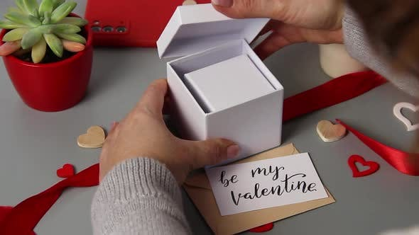 Somebody open a valentine's day gift box, message BE MY VALENTINE