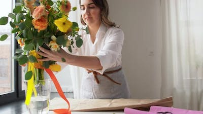 Woman Wrapping Flowers to Craft Paper at Home