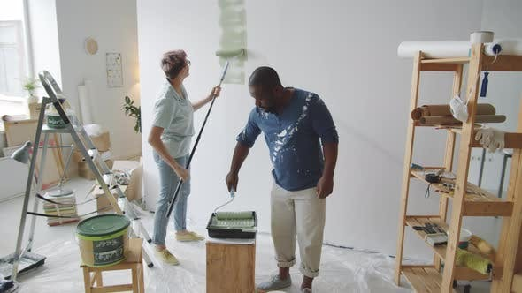 Multiethnic Couple Painting Walls Together