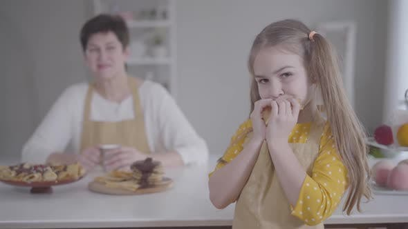 Thumbnail for Portrait of Cute Little Girl Eating Pancake with Blurred Caucasian Grandmother Smiling at the